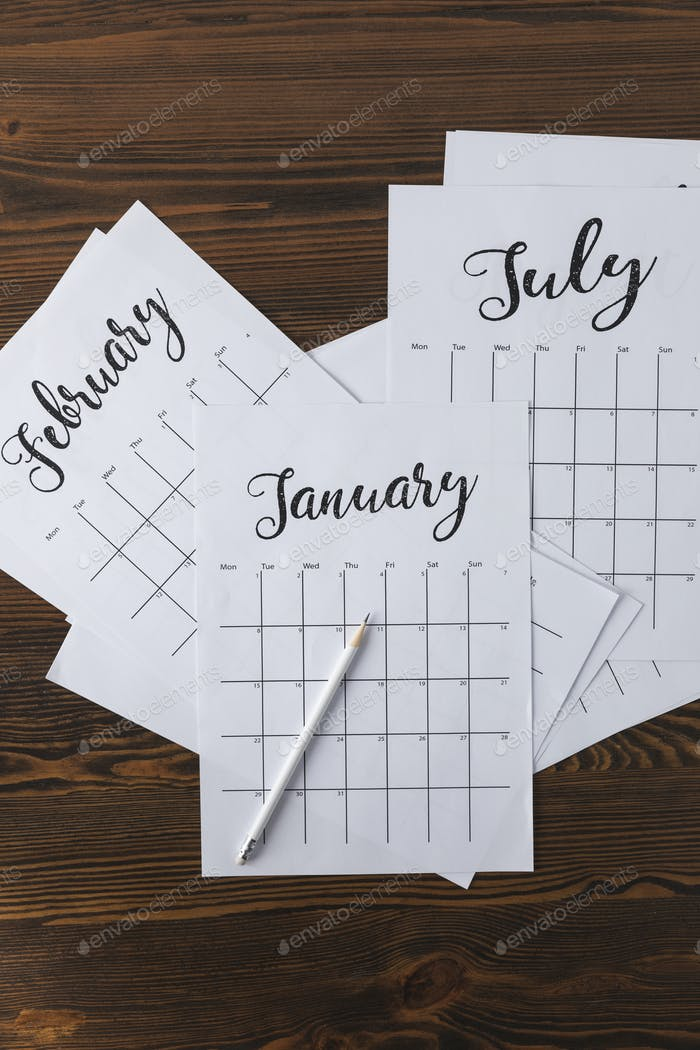flat lay with arranged calendar papers and pencil on wooden tabletop