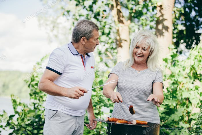 Happy elderly couple barbequing together.