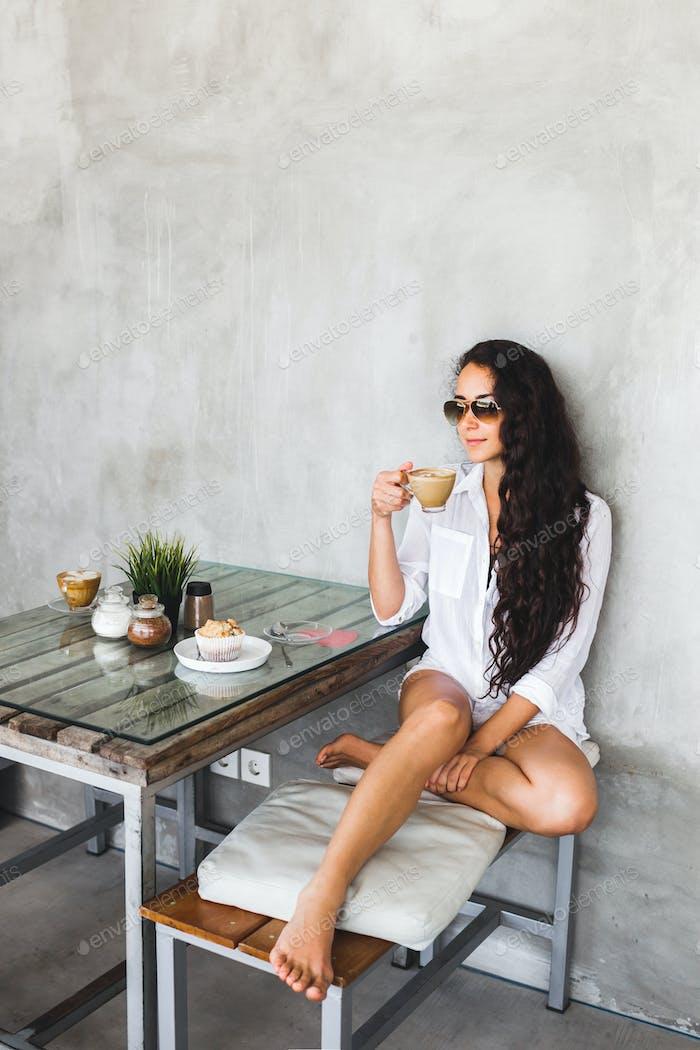 Joven morena bebe café en el moderno café loft con paredes de cemento y texturizado