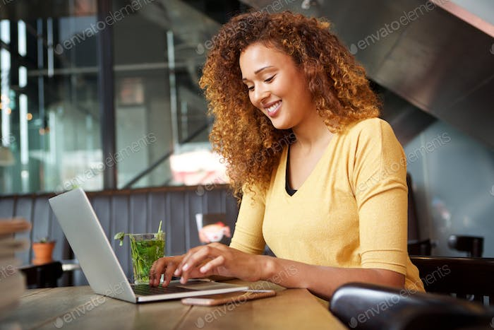 attractive young woman sitting at cafe and working with laptop