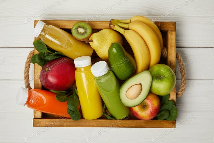 top view of fruits and detox smoothies in wooden box