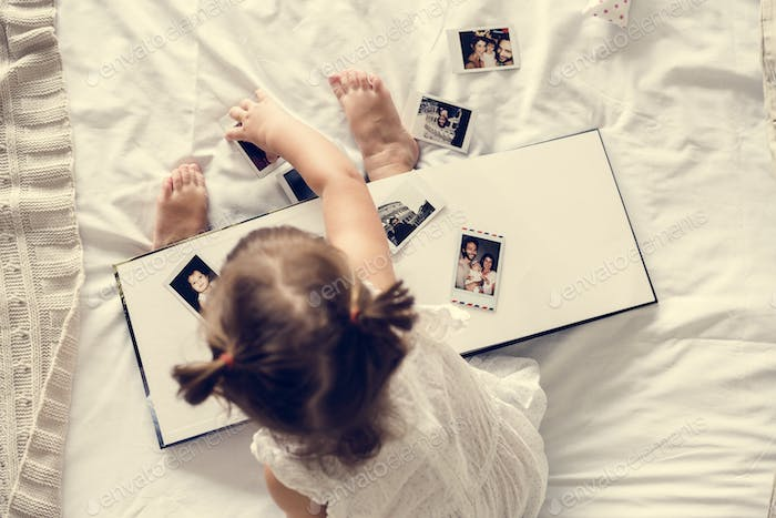 Little girl playing with a photo album