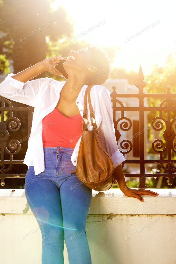 Cheerful woman talking on cell phone with bright sunlight