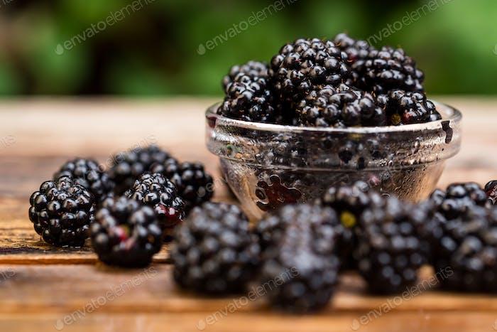 Fresh ripe blackberries in bowl on wooden table