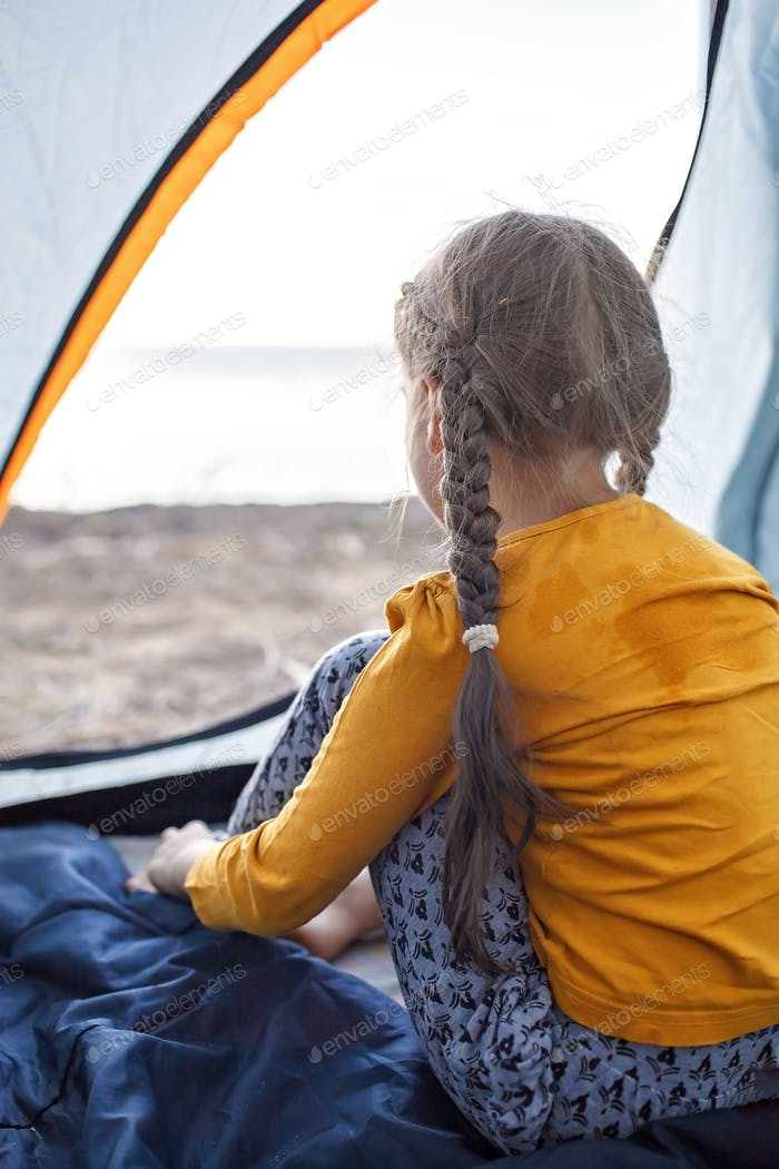 Family local getaway. Kid having rest in the camping tent at campsite, active lifestyle