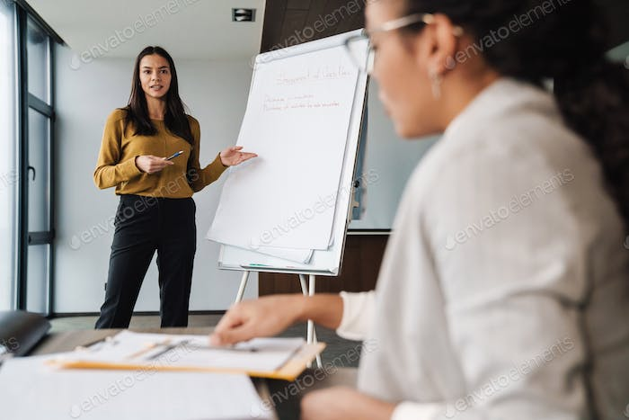 Portrait of businesswomen using flipchart while working in office
