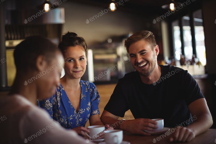 Happy friends interacting while having coffee