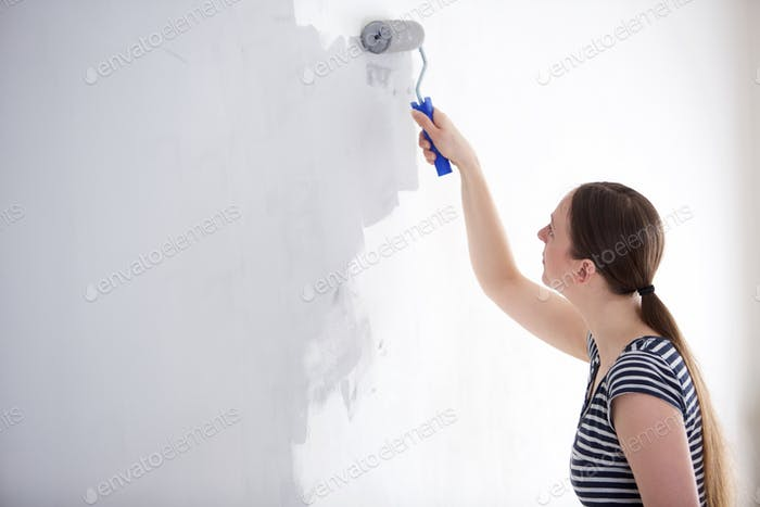 young woman painting wall of her home