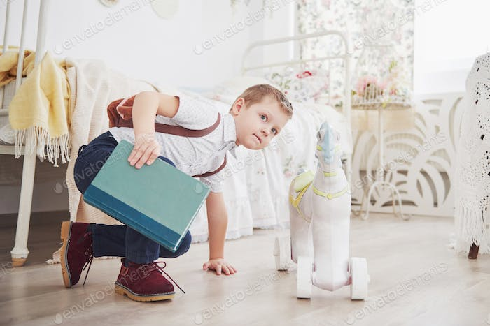 Child with school bag and book. Kid makes a briefcase, child room on a background. Back to school