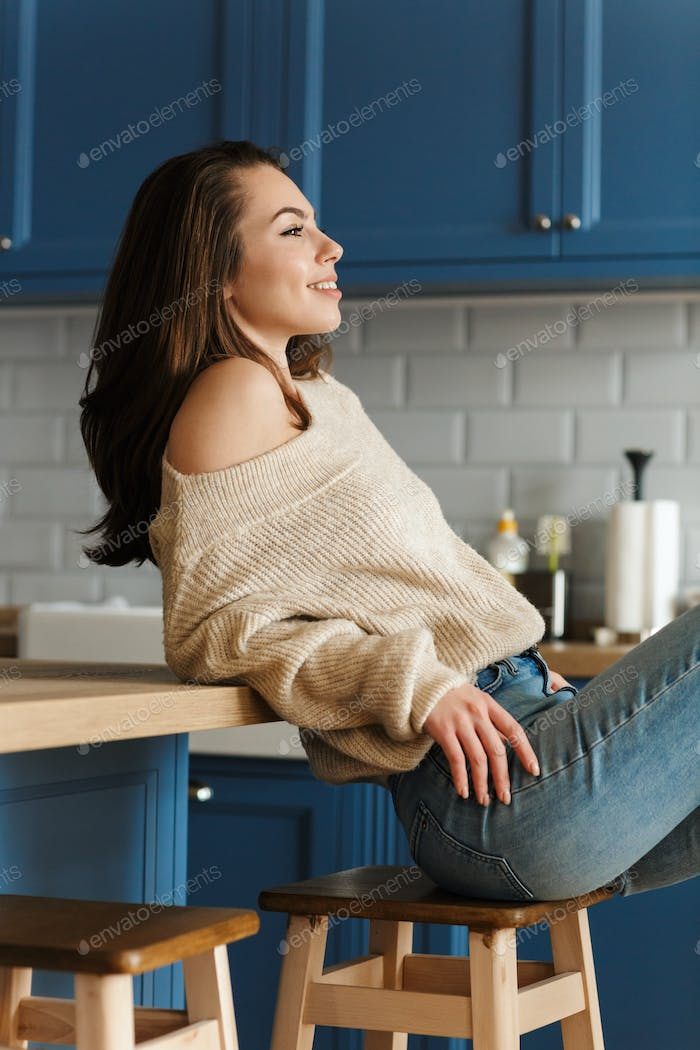 Beautiful young sensual woman sitting on a kitchen chair