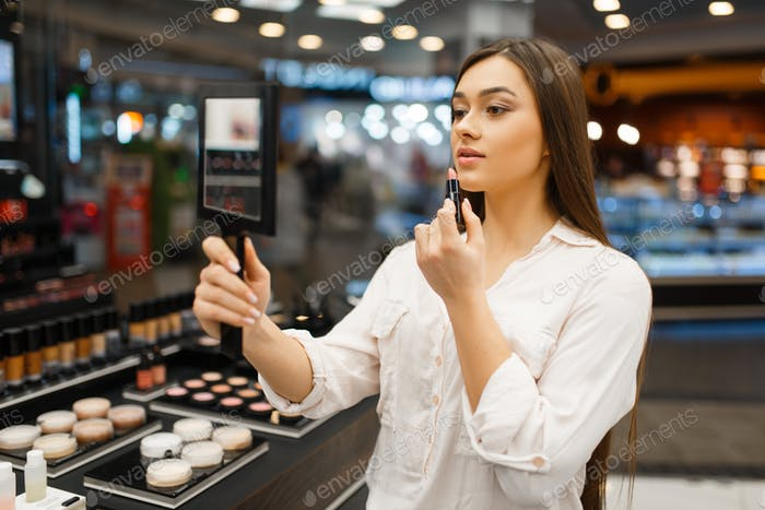 Woman with mirror applies lipstick in store