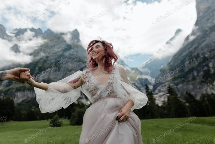 Happy Bride in Wedding Dress Holding Hands With Groom on Meadow With Mountains and Clouds in Alps