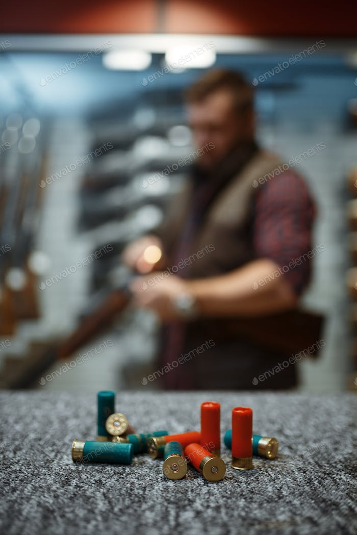 Ammo on counter, man loads a rifle on background