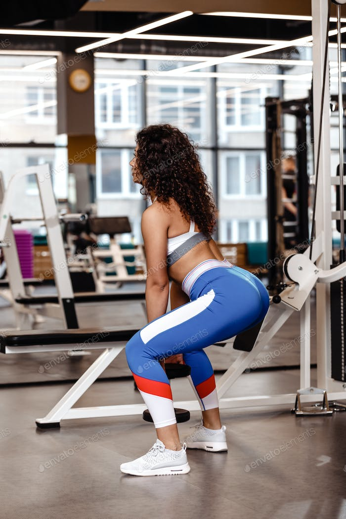 Pretty slim girl with dark curly hair dressed in a sportswear is doing back squats with heavy