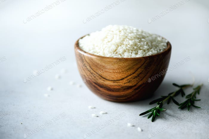 White raw organic jasmine rice in wooden bowl and rosemary on light concrete background. Food