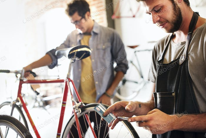 Two men in a cycle repair shop, one holding a smart phone and credit card. Paying by contactless