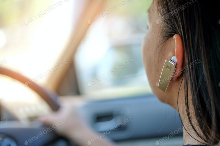 Women using hands-free phone while driving.