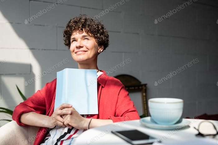 Pretty young woman with open book or notebook getting inspired on sunny day