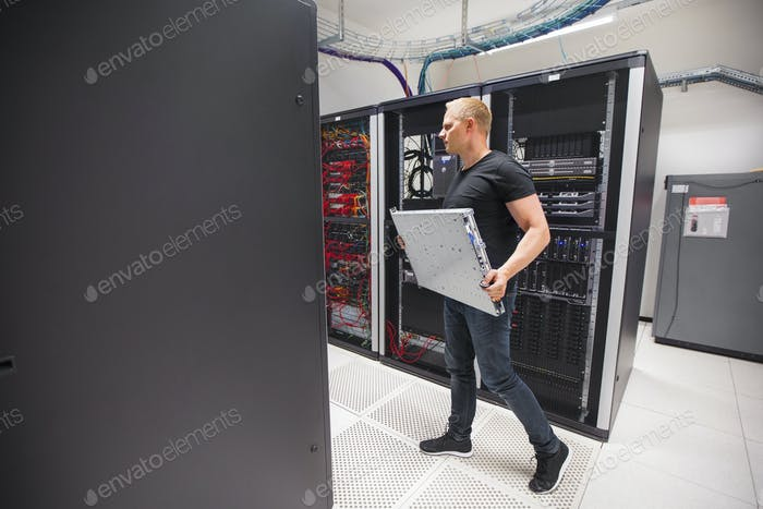 IT Engineer Carrying Blade Server While Walking In Datacenter