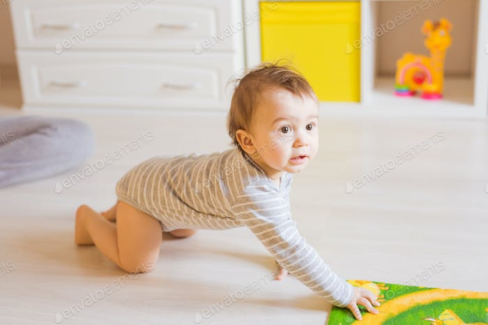 Portrait of crawling funny baby boy indoors at home