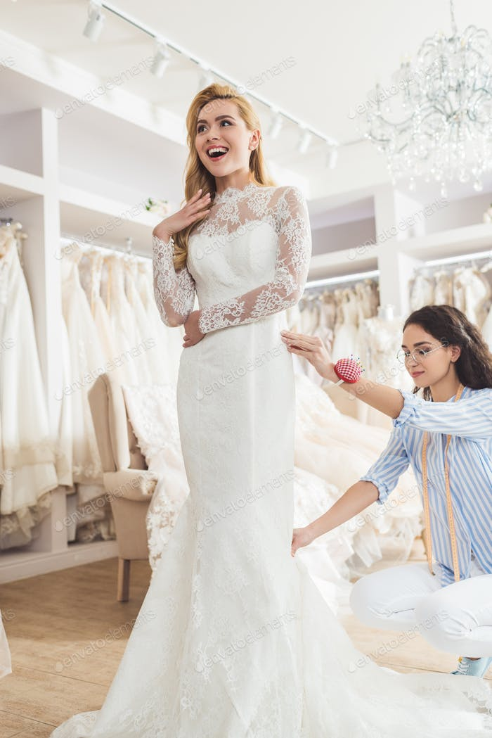 Blonde bride in lace dress and tailor during dress fitting in wedding salon