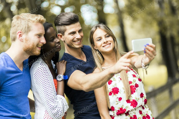 Group of young people and couples taking selfies in nature