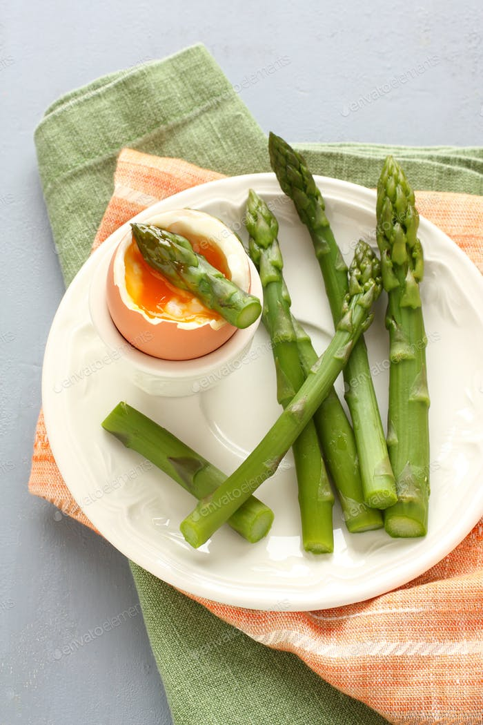 Green asparagus with soft-boiled egg on white plate