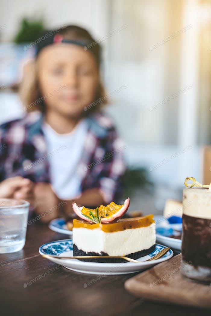 Вкусный торт за столом с вилкой на фоне размытого малыша