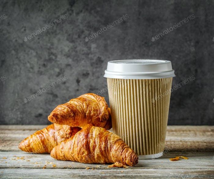 Tasse Kaffee und frisch gebackene Croissants