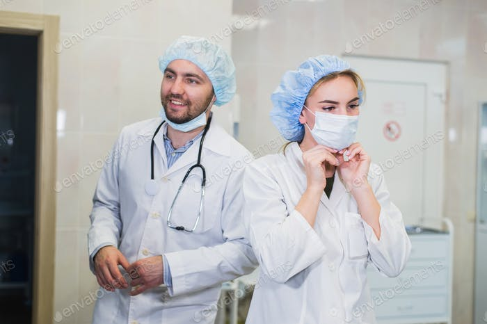 Confident female doctor putting on medical face mask while preparing for operation, her male