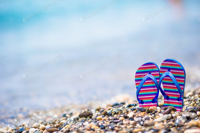 Kids flip flop on beach in front of the sea