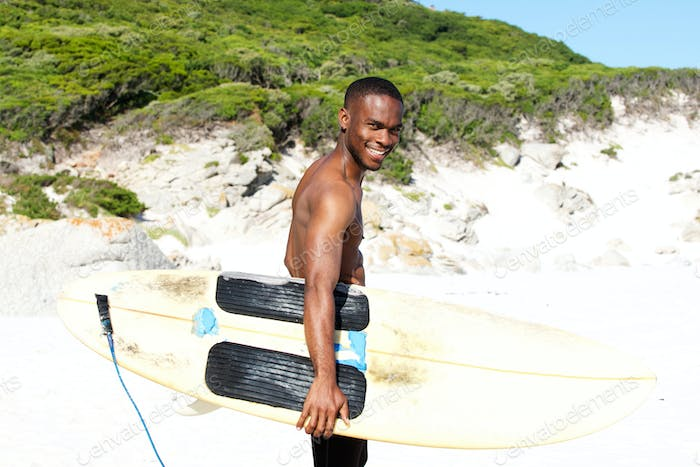 Smiing young african man at beach with surfboard