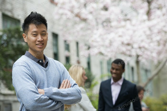 A man with his arms folded and two people talking in the background under the trees in blossom.