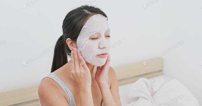 Woman apply facial paper mask on face at home