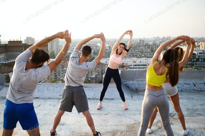 Group of fit happy sporty people exercising outdoors