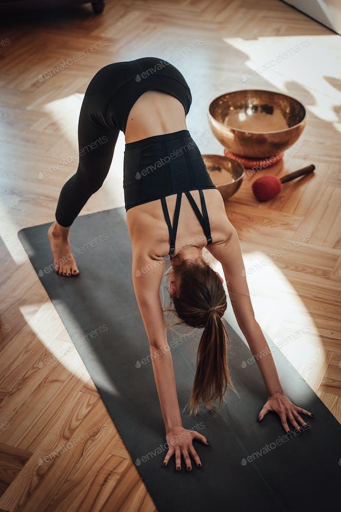 Portrait of a sportswoman doing yoga on mat in living room