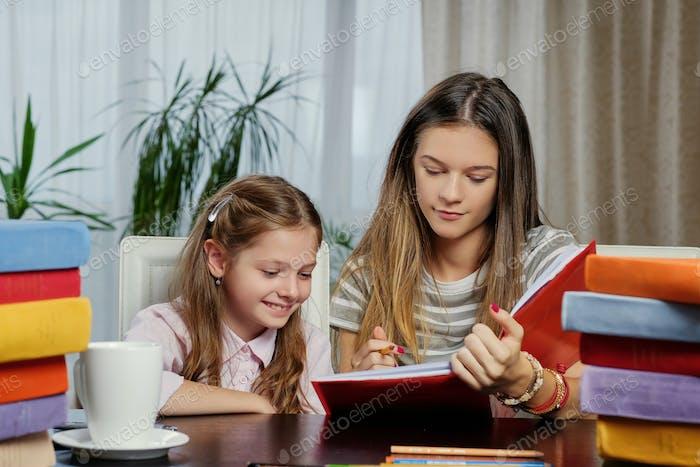 Подружки учатся за столом с большим количеством книг.