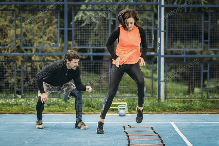Young Woman Exercise using Agility Ladder, working with Fitness Coach