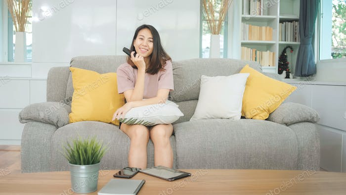 Young Asian teenager woman watching TV at home.