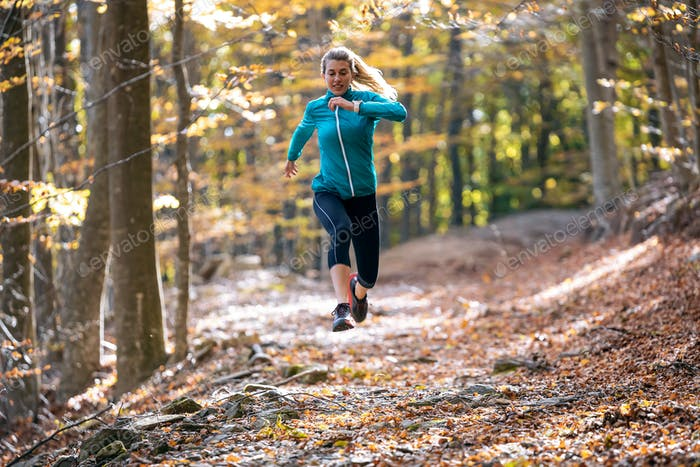 Sporty young woman running in the park in the autumn morning.