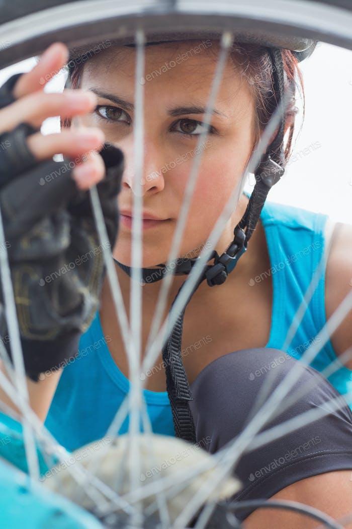 Focused woman adjusting her spokes on bike wheel in the countryside