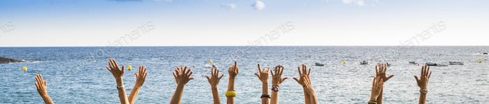 group of female hands in panoramic style with ocean in background