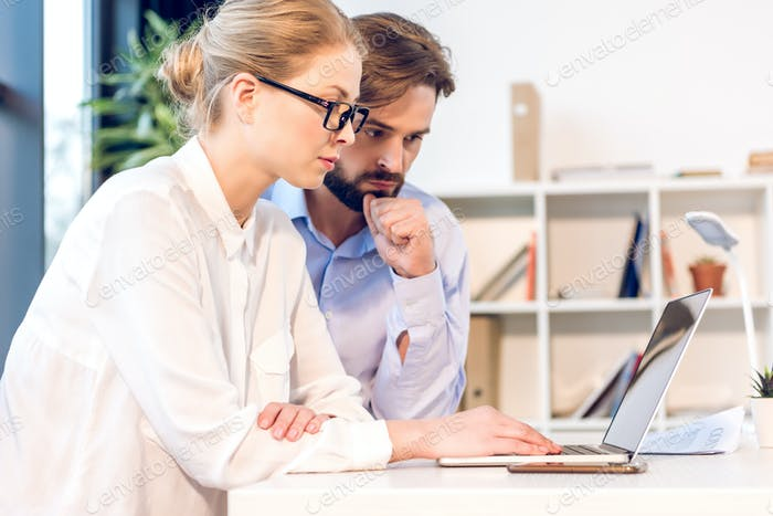 concentrated businessman and businesswoman with eyeglasses working with laptop in office