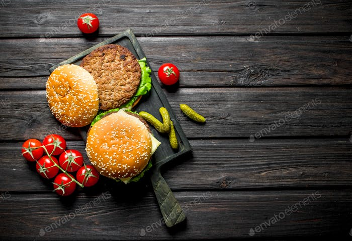 Burgers with tomatoes on a branch and gherkins.
