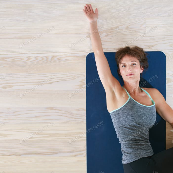 Woman lying and stretching on exercise mat