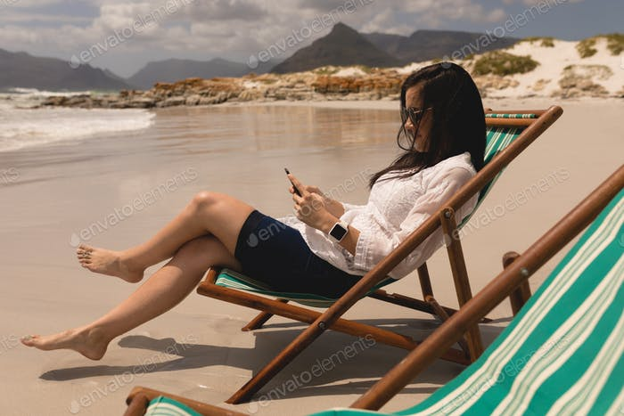 Beautiful young woman relaxing on sun lounger and using mobile phone at beach in the sunshine