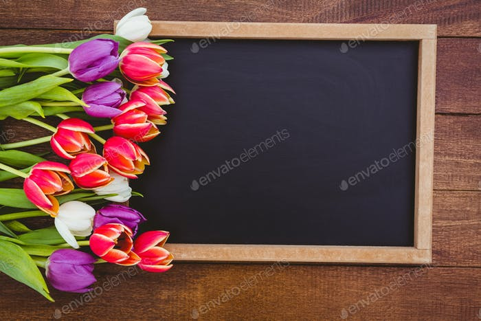 Bouquet of colored flowers against black board on wood desk