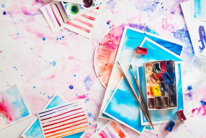 Lugar de trabajo de artista femenino con acuarela y bocetos