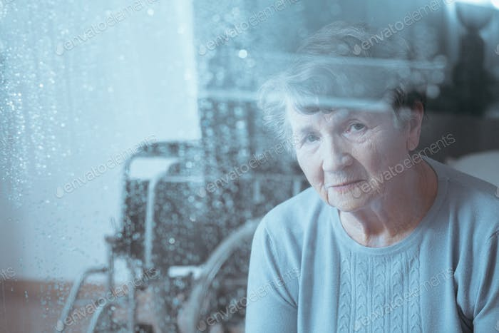 Sad, senior disabled woman