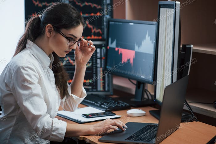 Mujer que trabaja en línea en la oficina con múltiples pantallas de ordenador en los índices